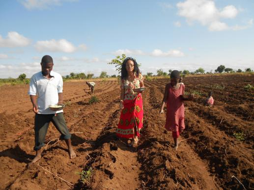 Mercy Nyirongo, alumna of Africa University, plants maize with orphans in a field in Malawi.