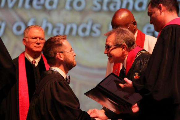 Bishop Gary Mueller (center, right) ordains the Rev. Jacob Lynn elder during the 2015 Arkansas Annual Conference.