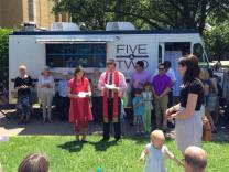 Pastoral staff bless the Five & Two food truck at a dedication ceremony.