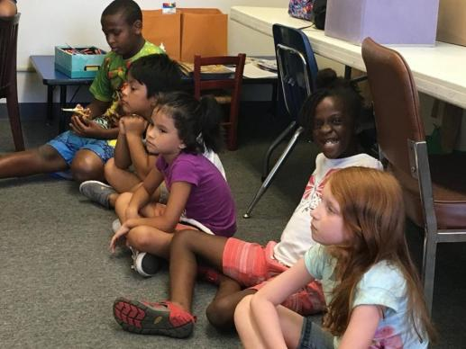 Children from First Grace United Methodist Church listen to their vacation Bible school lesson.
