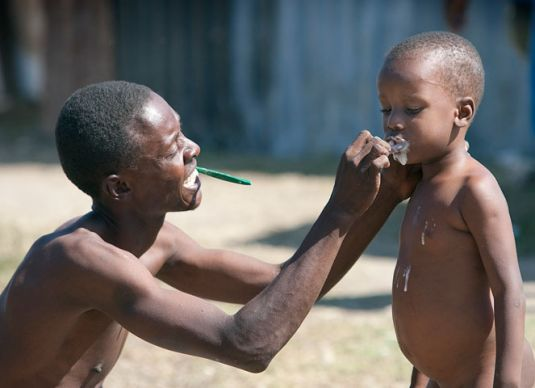 A father helps his son with basic hygiene at a makeshift camp in the municipal soccer stadium in Leogane, Haiti, following the earthquake.