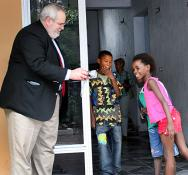 The Rev. Sam Dixon shares a digital photo with children during a visit to Kinshasa, Democratic Republic of the Congo, in December 2007.