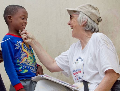 Volunteer Kathy Ahmad (right) visits with Franckenson Renevil during a break from renovating the Methodist Children's Home orphanage in Port-au-Prince, Haiti.