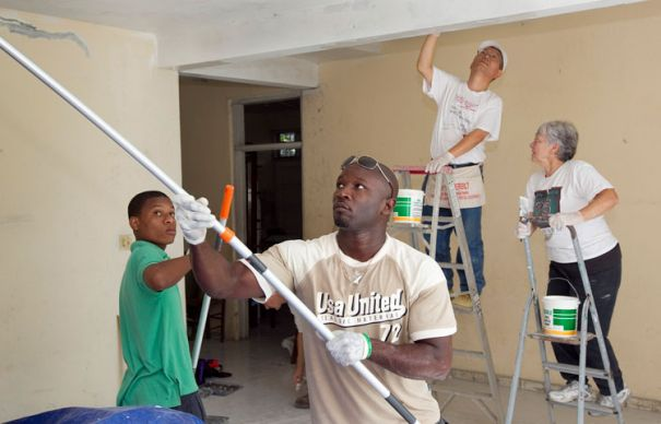Haitian and U.S. volunteers work together to paint the home of