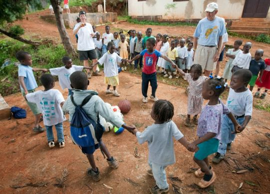 Volunteer in Mission team members Terry Temple (left background) and John Thomas (right background) help lead a game for children outside the Methodist church in Furcy, Haiti.