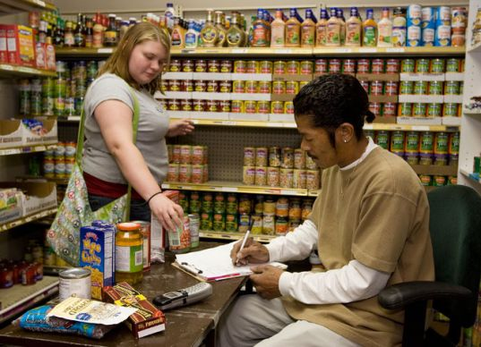 Alfred Hardnett (right) helps Candice K. Mink with her groceries in the food pantry at The Community Enabler Developer ministry in Anniston, Ala.. Photo by Mike DuBose, UMNS.