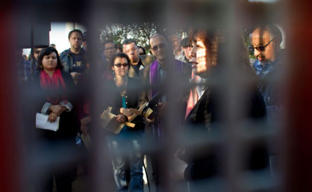 United Methodist Bishop Minerva Carcao is framed by the tightly-spaced mesh of the border fence between San Diego and Tijuana, Mexico, during the observance of Posada Without Borders. Today Carcao was among a group of religious leaders who spoke with President Obama about immigration reform.