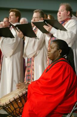 Adejumoke Onatunde of Nigeria, backed by the Mass Choir from United Methodist Seminaries, plays the drum during morning worship at the United Methodist Church's 2004 General Conference in Pittsburgh. A UMNS photo by Mike DuBose.