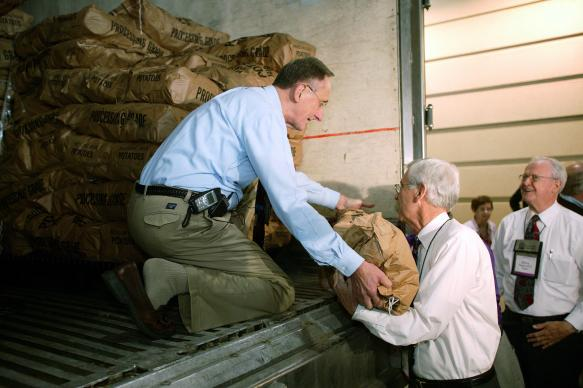 United Methodist Bishop Donald A. Ott (left) hands a sack of potatoes to Bishop Marshall L. (Jack) Meadors, Jr. during a Potato Drop outside the David L. Lawrence Convention Center in Pittsburgh, site of the denomination's 2004 General Conference. Preparing to receive the next sack is Bishop Ray Owen (right). The event, sponsored by the General Commission on United Methodist Men and the Society of St. Andrew, will help feed 120,000 of the city's hungry. A UMNS photo by Mike DuBose.
