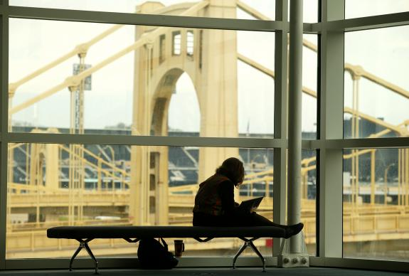 Katy Hinman, a member of the General Conference Choir from Candler School of Theology, finds a quiet spot to study her music in Pittsburgh's David L. Lawrence Convention Center, site of the 2004 General Conference. In the background is the 9th Street Bridge over the Allegheny River. A UMNS photo by Mike DuBose.