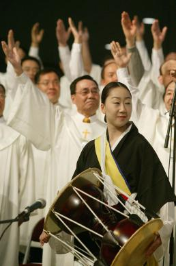 Yu Sun Kwang, flanked by other members of the choir from First United Methodist Church in Flushing, N.Y., plays a Korean drum during worship on May 3 at the denomination's 2004 General Conference in Pittsburgh. A UMNS photo by Mike DuBose.