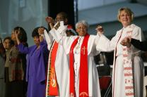 Holding hands during a service of appreciation for African Americans who stayed in the church despite institutional racism at the United Methodist Church's 2004 General Conference in Pittsburgh are, from left: Anne Marshall of the church's Commission on Christian Unity and Interreligious Concerns; Juanita Bryant of the Christian Methodist Episcopal Church; Jerry Ruth Williams; The Rev. Larry Pickens; and Bishops Violet L. Fisher and Charlene P. Kammerer. A UMNS photo by Mike DuBose.