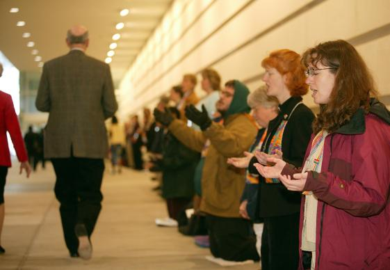 Laura Folkwein (right) and Elizabeth Brick (second from right) pray during a protest at General Conference. A UMNS photo by Mike DuBose.