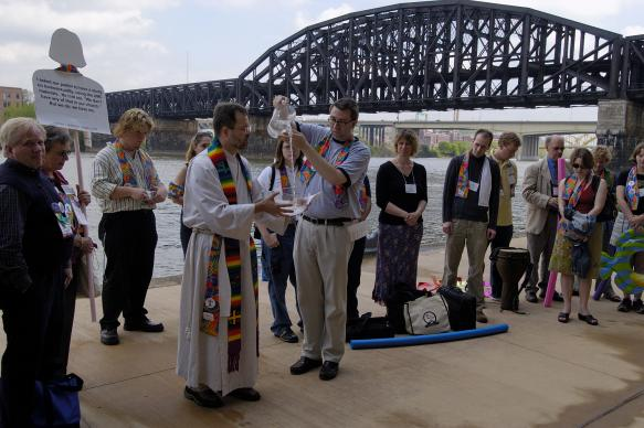 Members and supporters of Methodist Students for an All-Inclusive Church (MOSAIC) celebrate a renewal of the baptismal covenant on the edge of the Allegheny River, near Pittsburgh's David L. Lawrence Convention Center, site of the 2004 United Methodist General Conference. The group is pushing the denomination to fully accept gays and lesbians in its churches and pulpits. A UMNS photo by Paul Jeffrey.