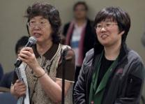 Translator Jungrea Chung (left) helps delegate Susan Nam of the Korean Methodist Church address an orientation for international delegates at the 2012 United Methodist General Conference in Tampa, Fla. A UMNS photo by Mike DuBose.