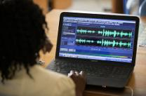 Patricia Ohomon edits audio in the newsroom of The United Methodist Church's Voice of Hope radio station in Abidjan, Côte d'Ivoire. Photo by Mike DuBose, UMNS