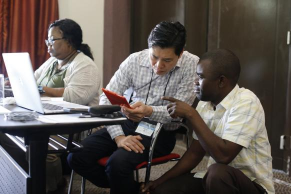 Danny Mai (center) helps Isaac Kunda Muke with a question during the training for Congolese church communicators. Mai and Shelia Mayfield (far left) were part of the team from United Methodist Communications, which held the training. Photo by Kathleen Barry, UMNS.