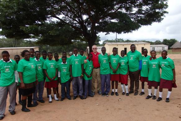 Dave Bonney, and students from Hanwa Secondary School in Macheke, Zimbabwe, pose in front of their school building. In March of 2016, Bonney visited the school to help set up a program called Helping Others Help Others to improve scholastic achievement at the small, rural school. Photo courtesy of Dave Bonney.