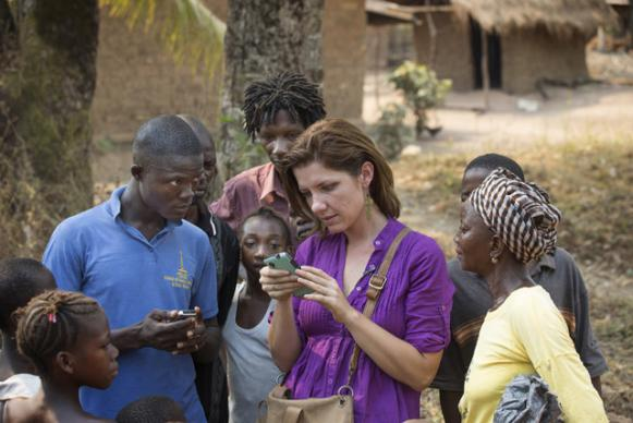 Maeghan Orton (center, in purple shirt) visits with villagers in Bumpe near Bo, Sierra Leone, about mobile phone technology. Orton is from Medic Mobile, a technology partner of United Methodist Communications. Photo by Mike DuBose, UMNS.