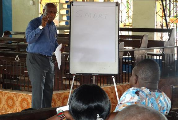 Dr. Victor Masssaquoi talks to district lay leaders at a training session in Bo, Sierra Leone, on goal setting in June, 2016. Photo by Phileas Jusu, UMNS.