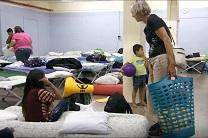 A volunteer chats with immigrants resting on cots at The Inn, a temporary shelter run by United Methodist churches in Arizona to house migrants coming out of immigration detention centers. Video image courtesy of United Methodist Communications.