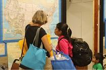 A volunteer looks at a map of the U.S. with a migrant mother at The Inn, a temporary shelter run by United Methodist churches in Arizona for families coming out of immigration detention centers. Video image, courtesy United Methodist Communications.