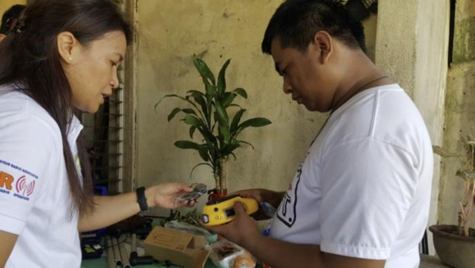 Pastor Jucar Tabunan (right) receives a Freeplay solar radio from April Mercado as part of the 2016 Typhoon Haima disaster response. Photo courtesy of April Mercado, United Methodist Communications.