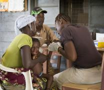 Health worker Juliana Koroma (right) takes a blood sample from Issata Jusu for a malaria test at the Koribondo Community Health Center near Bo, Sierra Leone. Holding the child is her is her mother, Umu Koroma. At rear is health worker Ishmael Karoma. Photo by Mike DuBose, UMNS.