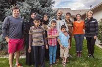 Members of the Cathedral of the Rockies First United Methodist help Syrian refugees, the Al Aboud family, get settled in their new home. Photo by Kisker Productions.