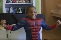 A child tries on a Spiderman outfit at the Nashville Costumes for Kiddos Project shop. Video image by United Methodist Communications.