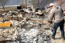 Volunteer cleans up debris in the aftermath of the recent wildfires that destroyed homes and businesses in Gatlinburg, Tennessee. Photo courtesy of The Daily Times.