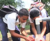 Children get water from a pump in video about global health efforts of The United Methodist Church. Video image courtesy of Board of Global Ministries.