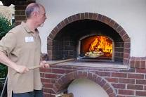Gil Kruger, a member of Hamline Church United Methodist in St. Paul, Minnesota, bakes a pizza in the congregation's new outdoor oven. Video image by United Methodist Communications.