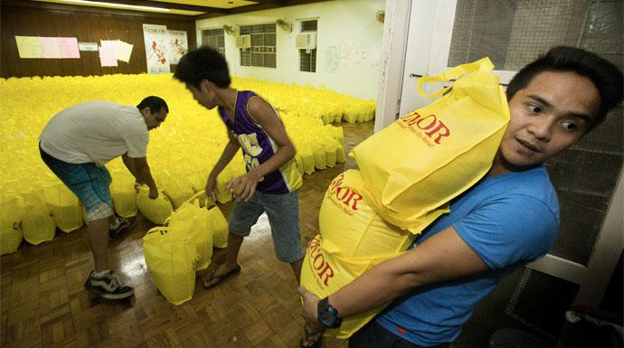 Volunteer Vincent Salazar (right) helps a team with the United Methodist Committee on Relief in Manila as they load bags of relief supplies for survivors of Typhoon Haiyan in the Philippines. Photo by Mike DuBose, United Methodist Communications.