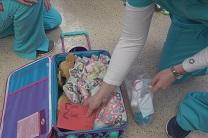 Volunteers pack a suitcase for a foster child for Love on Wheels. Video image by United Methodist Communications.