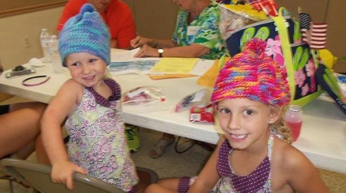 Piper (left) and Conleigh Wilhide   wear hats knitted by Virginia Fritts, a member of Surfside United Methodist Church. Photo courtesy of Surfside United Methodist Church.