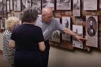 Jim Maag points out an item on a church history wall he helped create at First United Methodist Church of Topeka. Maag is on the archive team. Image from video by United Methodist Communications.