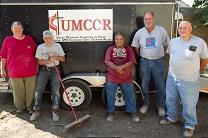 Members of a United Methodist Volunteers in Mission Team  from the Inidana Conference pose with homeowner Edward Ortiz (center) in front of the team's construction trailer in Minot, N.D. File photo by Mike DuBose, UMNS.