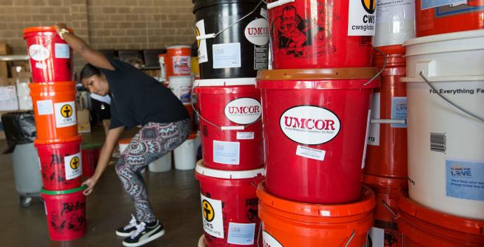 Edna Rajan stacks flood buckets from the United Methodist Committee on Relief at a United Way warehouse in Lafayette, La. Photo by Mike DuBose, United Methodist Communications.