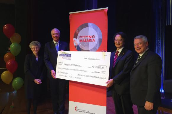 Bishop Jeremiah Park (second from right), presents check to Imagine No Malaria. Also pictured: Bishop Peggy Johnson (far left); Bishop Thomas Bickerton and Tom Willard, senior pastor at Camp Hill United Methodist Church (far right). Photo by Sandii Peiffer, Susquehanna Conference.