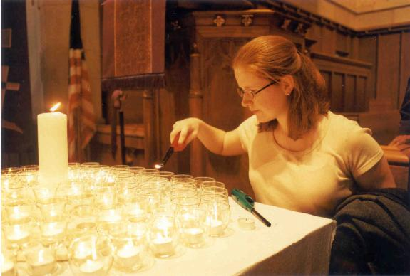 During a CVAC memorial service, a young girl lights a candle in memory of her brother who was killed during a robbery in Atlanta. Photo by Bruce Cook
