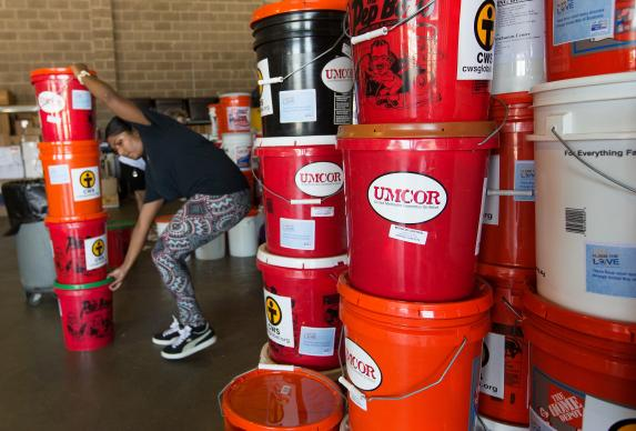 In August 2016, Edna Rajan stacks cleaning buckets from the United Methodist Committee on Relief at a United Way warehouse in Lafayette, La. Photo by Mike DuBose, UMNS.