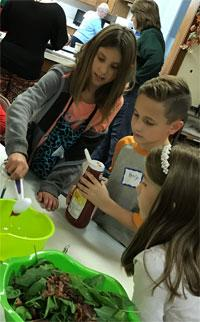 Making salad dressing is a team effort for Ava, Henry and Miley during cooking classes at Faith United Methodist Church in Genoa, Ill. Photo courtesy of Melissa Meyers