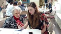 Aiden Taylor (right) provides Judy Johnson with tips on using her mobile phone. Photo by Christina Kincaid, Asbury Memorial United Methodist Church.