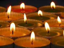 Votive candles lit to remember departed loved ones. Photo by Hans / Pixabay.com.