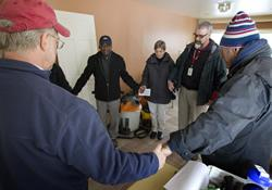 The Rev. Tom Hazelwood (second from right) of the United Methodist Committee on Relief leads a prayer for homeowners, family members and church volunteers at a home damaged by floodwaters from Hurricane Sandy in Massapequa, N.Y., on Long Island. The group wears heavy clothing against the cold because the home is without power.