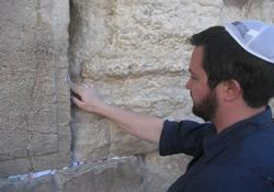 The Rev. Matthew W. Kelley places a prayer between stones of the Wailing Wall in Jerusalem.