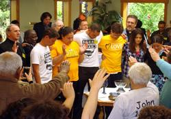 The congregation at Rising Hope United Methodist Mission Church in Alexandria, Va., forms a prayer circle around young people traveling along the east coast to raise awareness of immigration issues.