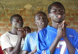 Young people in Uganda clasp their hands in prayer.