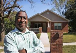 Proud homeowner Monte Payne stands in front of his brick bungalow in Little Rock, Ark.
